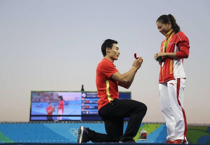 El chino Qin Kai se acercó al final de la premiación para darle una cajita con flores a He Zi, quien rápidamente le dijo que si al clavadista. (Wong Maye-E/AP)