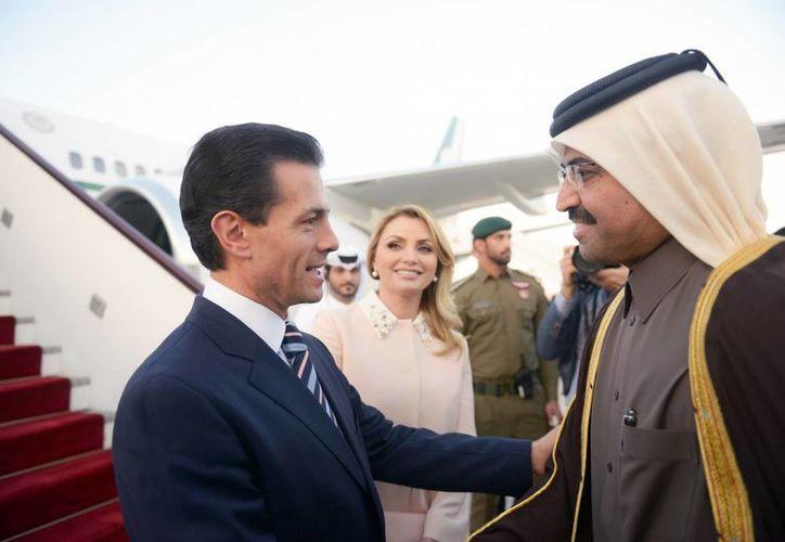 El presidente Enrique Peña Nieto acompañado de su esposa, Angélica Rivera, al llegar al Aeropuerto Internacional de Doha, capital de Qatar, donde habló del aumento del precio del dólar. (Notimex)