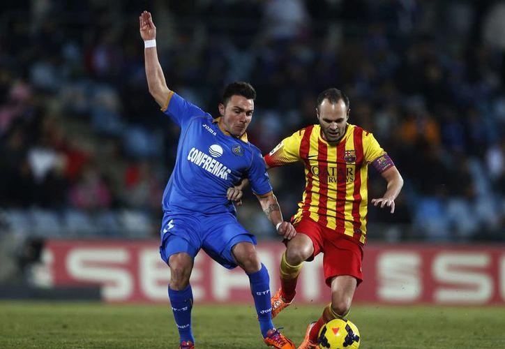 Iniesta (d) disputa el baló con Adrian Colunga en duelo que el Barcelona ganó por 5-2 ante el Getafe este fin de semana. Iniesta amplió su contrato con el Barza hasta 2018. (Agencias)