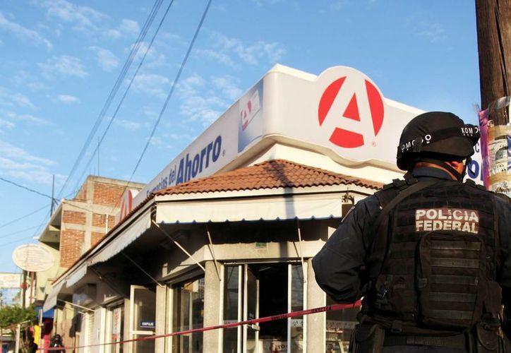 Las autoridades descartan que la militarización de Michoacán sea permanente. En la imagen, la farmacia siniestrada. (siete24.mx)
