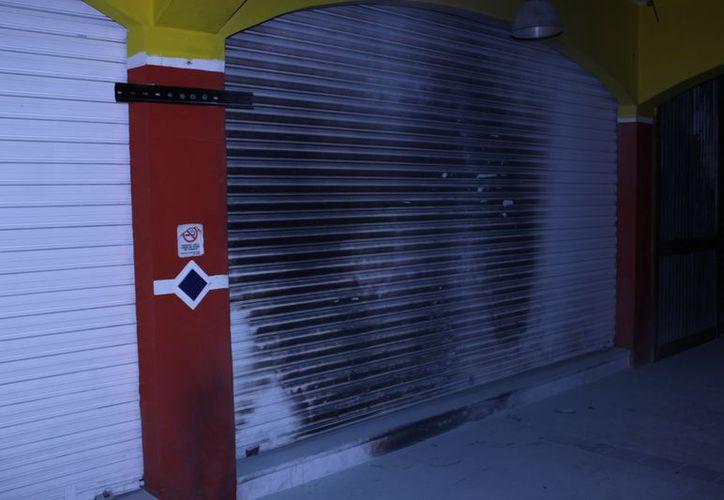 En uno de los negocios quemaron una de las cortinas. (Eric Galindo/SIPSE)
