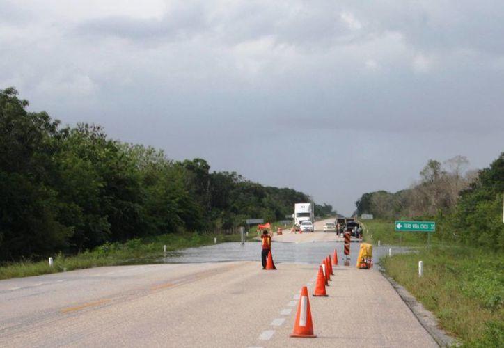 Las constantes lluvias han provocado encharcamientos en la zona, que implican un peligro más para quienes transitan por la vía. (Rossy López/SIPSE)