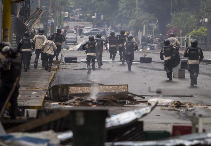 Miembros de la Policía Nacional Bolivariana (GNB) intentan dispersar un grupo de manifestantes opositores al Gobierno. (Archivo/EFE)