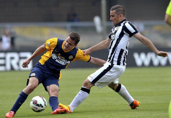 Juanito Gomez (i), del Hellas Verona, pelea el balón con Simone Padoin, de Juventus, en partido que terminó 2-2, aunque el cuadro de Turín jugó como campeón de antemano. (Foto: AP)