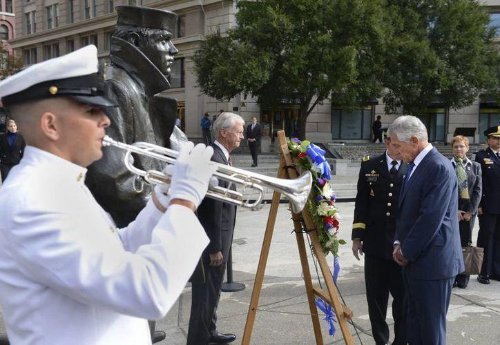 El secretario de Defensa estadounidense, Chuck Hagel (d), deposita una corona de flores durante una ceremonia en memoria de las víctimas del tiroteo. (EFE)