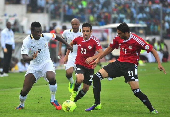 Gyan, autor del doblete (i) pelea por el balón contra Mohamed Naguib y Ahmed Shedid, de Egipto. (Agencias)