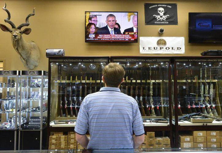 Un hombre observa el discurso del presidente Obama sobre el control de ventas de armas, desde una tienda de armas en Augusta, Georgia. (Agencias)