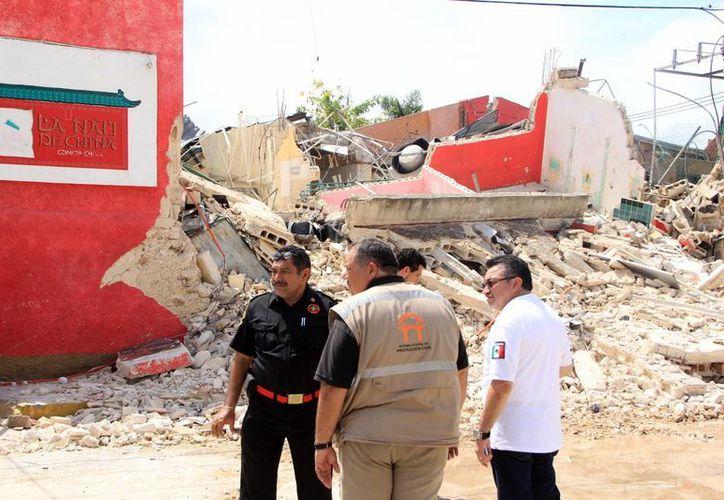 Bomberos y Protección Civil evaluaron la zona para determinar las causas del estallido que derrumbó el edificio. (SIPSE)