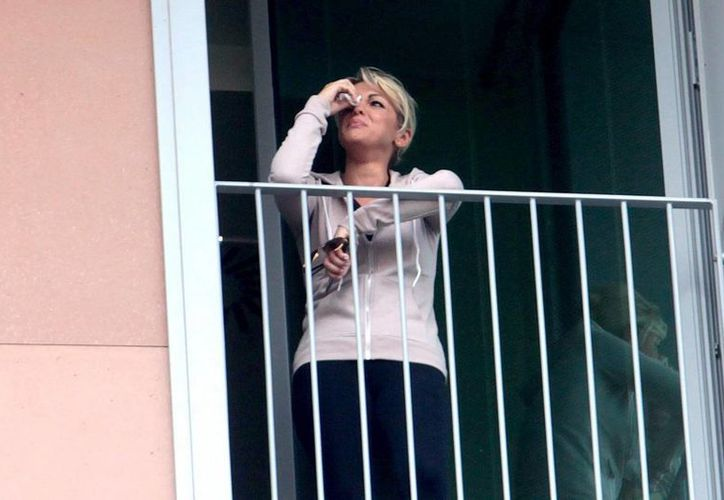 La prometida del ex primer ministro italiano Silvio Berlusconi, Francesca Pascale, se asoma a una ventana del hospital de San Raffaele en Milán durante la operación de 'Il Cavaliere'. (EFE)