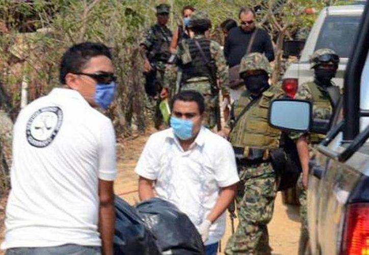 Los cadáveres fueron localizados envueltos en sábanas en un panteón del municipio de Chilapa, Guerrero. Imagen del levantamiento de los cuerpos por parte de las autoridades. (notisistema.com)