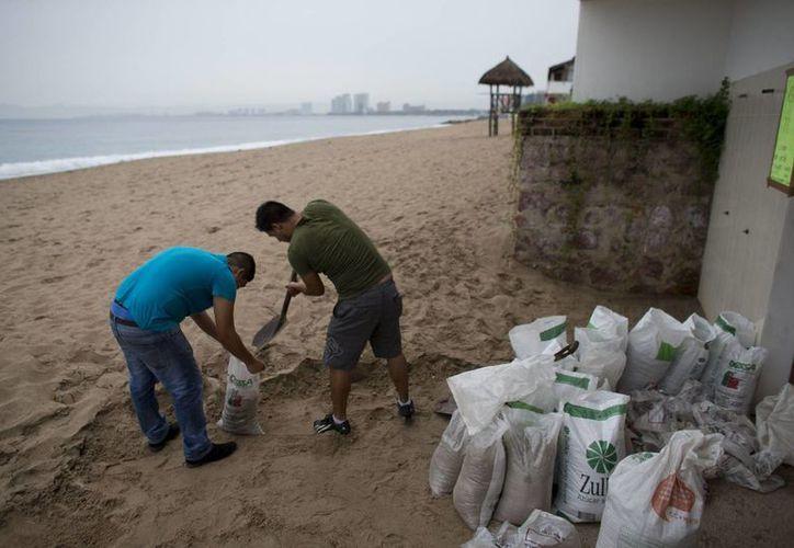 Dos hombres llenan pequeños sacos con arena en Puerto Vallarta, Jalisco, como media preventiva ante la llegada del huracán Patricia, que se prevé toque tiera esta tarde en costas del Pacífico mexicano.(AP Foto/Rebeca Blacwel)