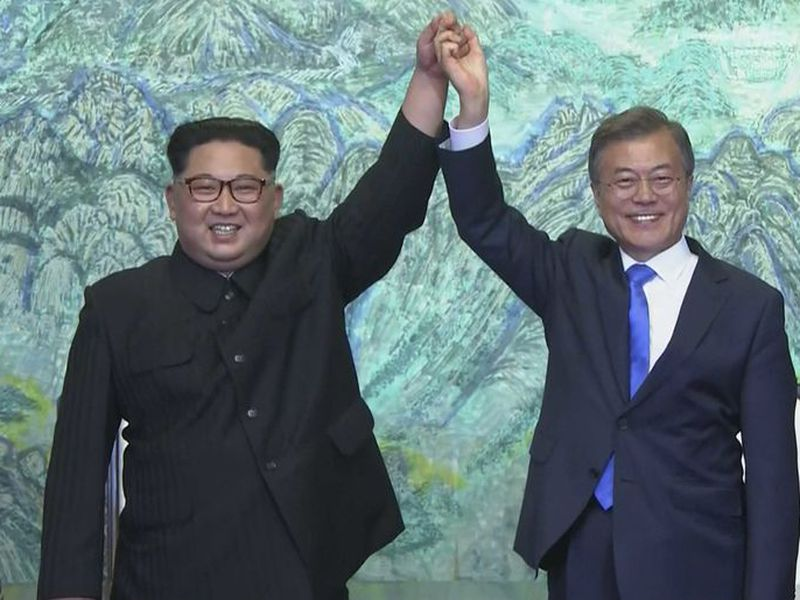 North Korean leader Kim Jong Un, left, and South Korean President Moon Jae-in raise their hands after signing on a joint statement at the border village of Panmunjom in the Demilitarized Zone. (AP)