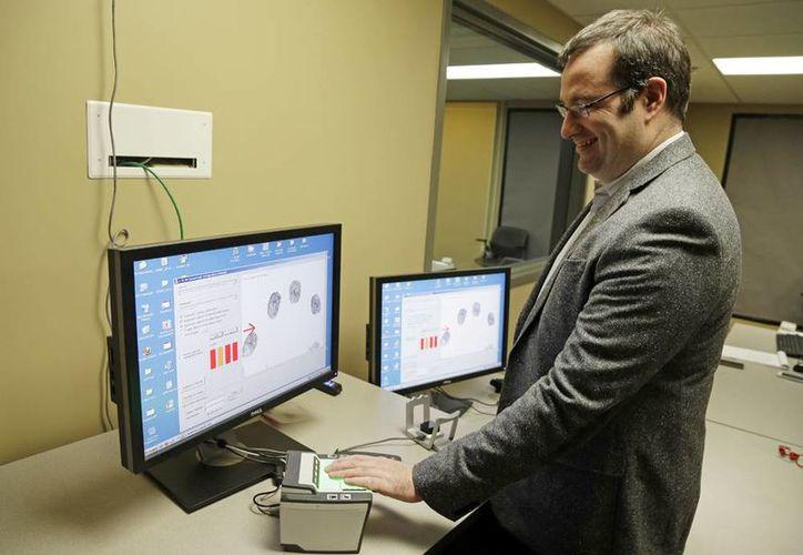 Stephen Elliott, director de Investigación Biométrica Internacional en la Universidad de Purdue, demuestra un sistema de reconocimiento de huellas digitales. (Agencias)