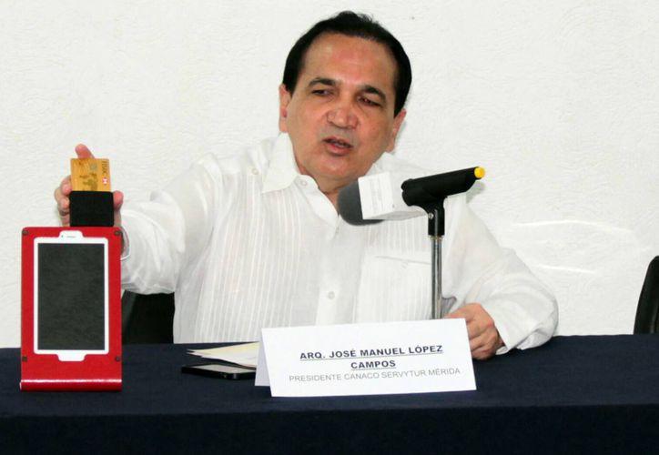 Imagen del presidente de la Canaco Servytur, José Manuel López Campos, al mostrar la tablet con una terminal lectora de tarjetas de crédito y débito. (Milenio Novedades)