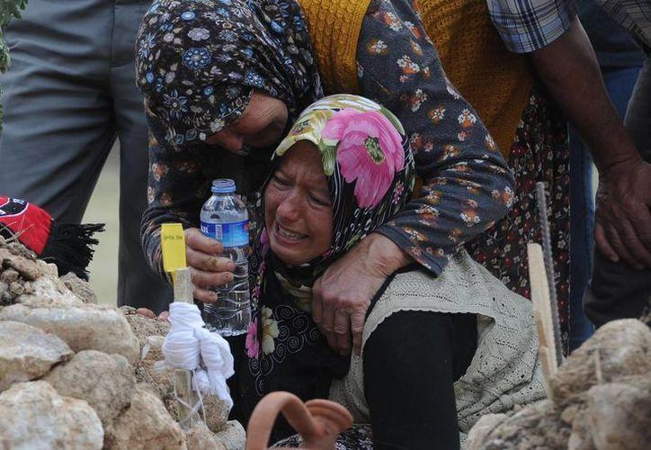 Familiares de un minero lloran ante su tumba en Soma, Turquía, donde ocurrió la más reciente tragedia minera. (Agencias)