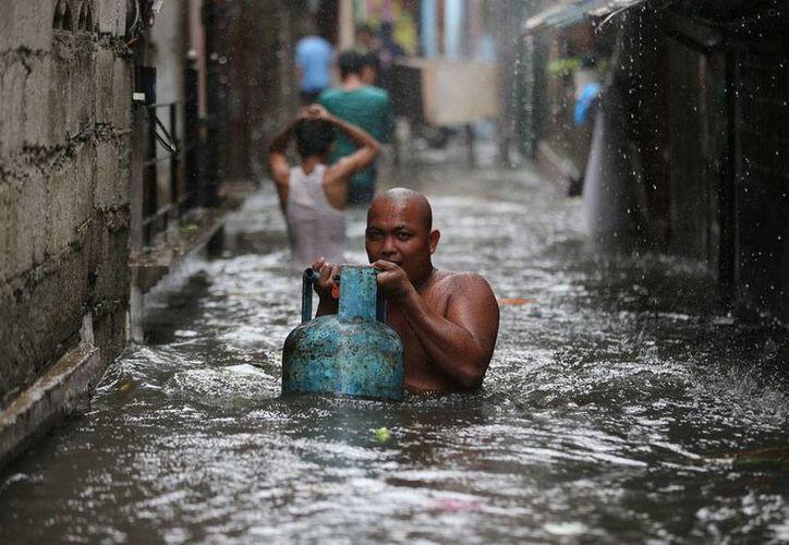 Como pudieron, los filipinos rescataron lo que el tifón Rammasun, que ha dejado hasta ahora más de 10 muertos, no pudo llevarse. (AP)