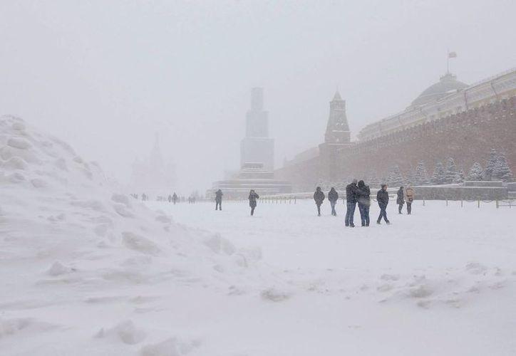 Moscovitas caminan por la Plaza Roja durante la primera gran nevada de este invierno en la ciudad de Moscú. (EFE)