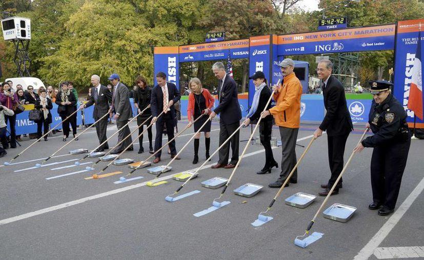Deportistas y funcionarios participan en la ceremonia de pintura de la línea de meta del maratón de Nueva York. (Agencias)