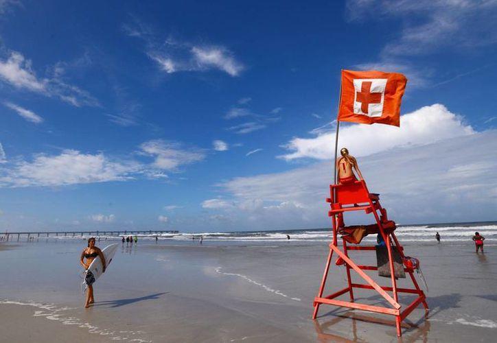 Con la tormenta Arthuh moviéndose hacia las Carolinas, esta mañana, en la playa de Jacksonville, Florida, aún había gente surfeando. (Foto: AP)