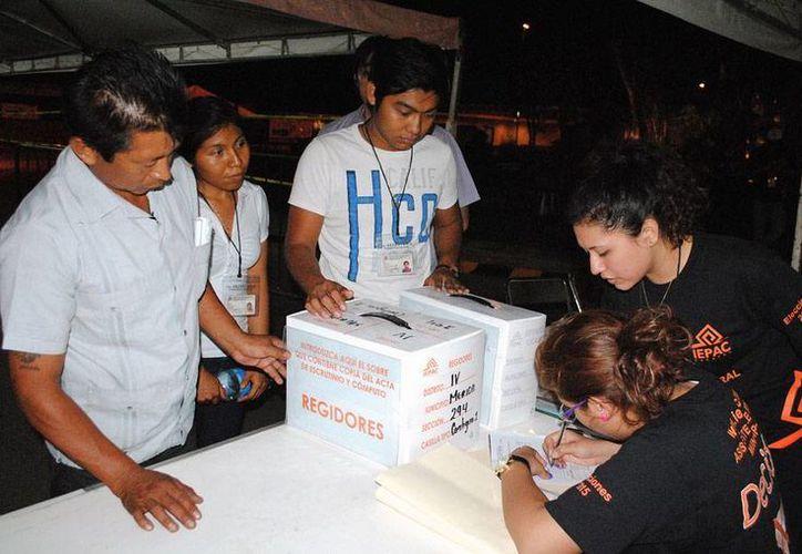 Los consejos electorales de Yucatán tuvieron que contar nuevamente los votos de 70 por ciento de los paquetes electorales. En la imagen -utilizada sólo con fines ilustrativos- funcionarios de casilla entregan un paquete para la elección de regidores de Mérida. (Archivo/Milenio Novedades)