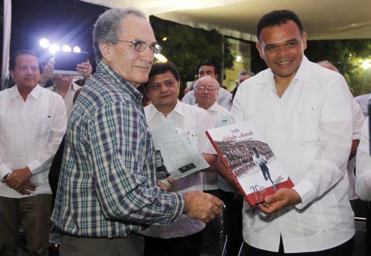 El editor Gaspar Gómez Chacón (i) con el gobernador Rolando Zapara durante la presentación del libro en torno a la historia del estadio Salvador Alvarado. (Milenio Novedades)