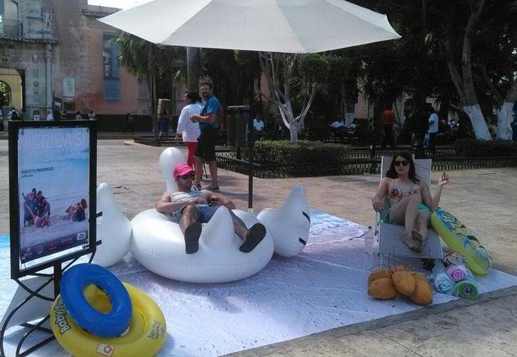 Una pareja de modelos se asolea todos los días en la Plaza Grande, como parte de la promoción turística 'Mérida sí tiene playa'. (Cecilia Ricárdez/SIPSE)