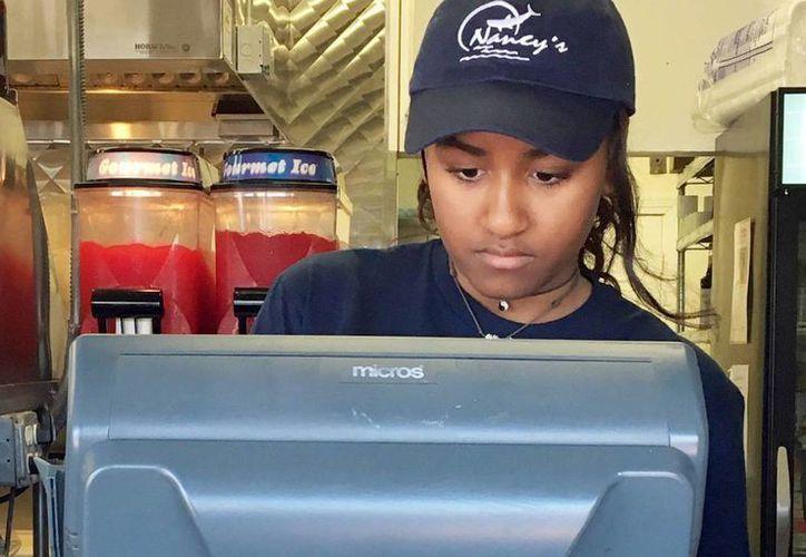 Imagen de Sasha Obama en su primer trabajo de verano, en un restaurante de mariscos en Estados Unidos.(Christopher Evans Boston Herald/Polaris)