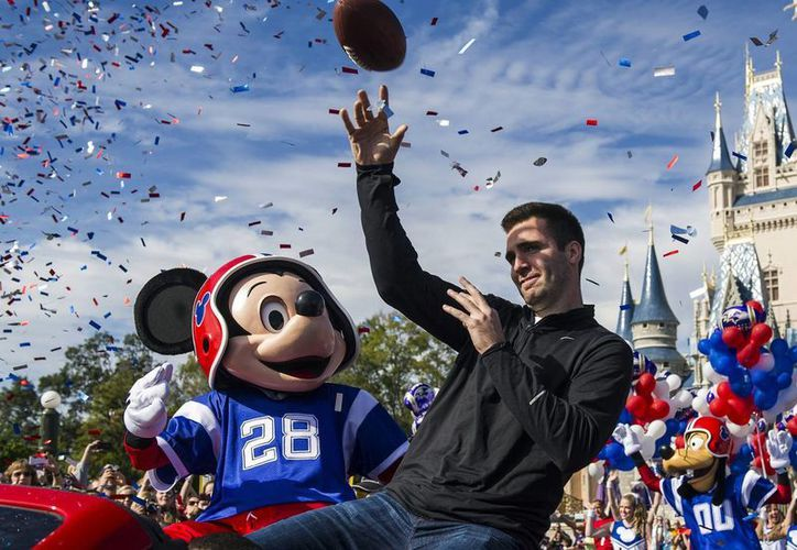 Joe Flacco, mariscal de Ravens, juega con Mickey Mouse en el desfile realizado ayer en el Magic Kingdom, en Walt Disney World. (Agencias)