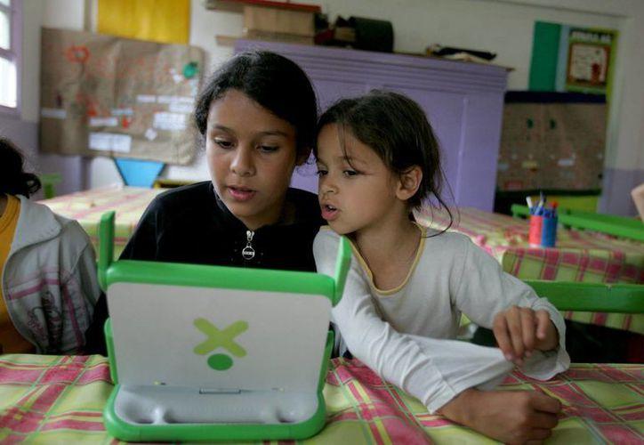El plan contempla garantizar la entrega de una computadora portátil por estudiante en edad escolar para su formación. (Archivo/EFE)