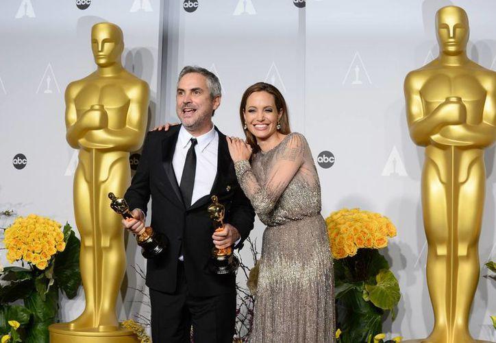 Alfonso Cuarón con Angelina Jolie, quien fue presentadora en la 86 entrega del Oscar. (Agencias)