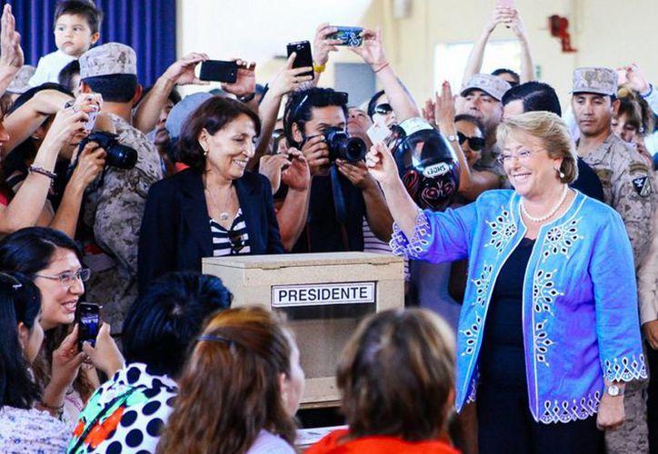 La candidata presidencial del bloque opositor Nueva Mayoría de Chile, Michelle Bachelet, al depositar su voto. (Notimex)