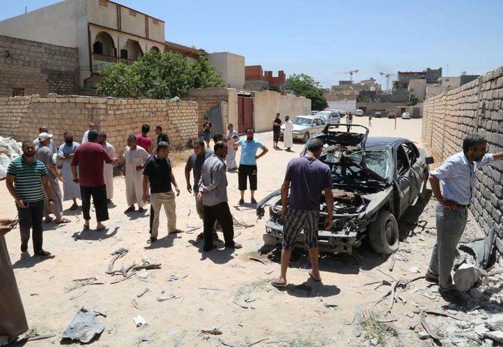 Revisión del lugar donde impactaron unas granadas, este 23 de julio de 2014, durante los combates en torno al Aeropuerto Internacional de Trípoli. (EFE)