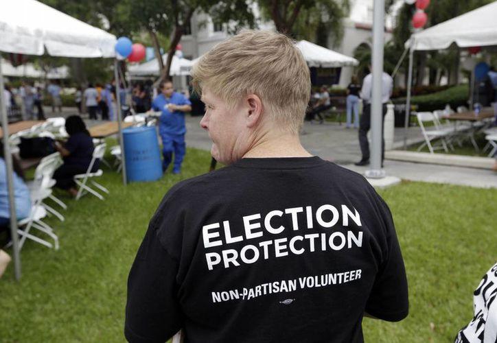 Una voluntaria de un grupo que invita a los ciudadanos estadounidenses a votar, durante la apertura de las elecciones tempranas en Florida. (AP/Lynne Sladky)