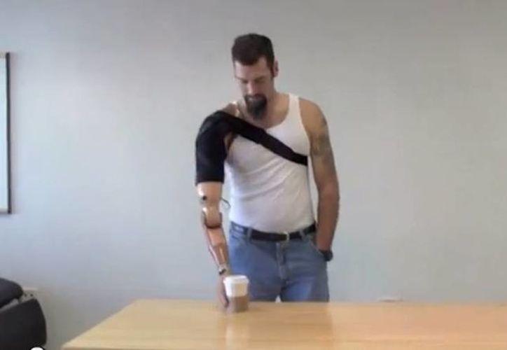 Un exoficial del Ejército herido en Irak demuestra cómo funciona el brazo artificial al conectarse a los músculos. (YouTube)