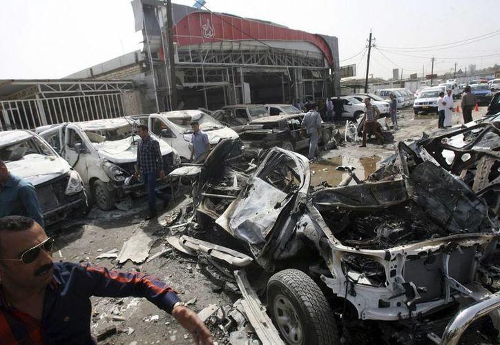 Un grupo de civiles examina el concesionario donde fue perpetrado un ataque con bomba, en el distrito Nahda, en Bagdag, Irak. (EFE/Archivo)