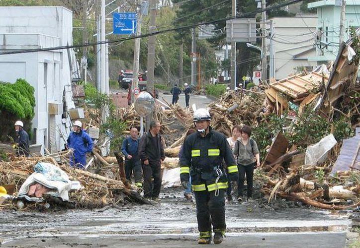 Los equipos de rescate y residentes caminan entre los escombros de las casas en Oshima, las cuales fueron dañadas por deslizamientos de tierra. (Agencias)
