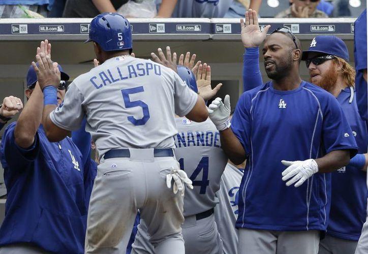 El avión con los jugadores tuvo un aterrizaje de emergencia. Imagen de Alberto Callaspo (5) al ser recibido por sus compañeros de equipo después de anotar dos carreras en el partido de ayer entre Dodgers de Los Angeles contra los Padres de San Diego. (Foto AP / Gregory Bull)