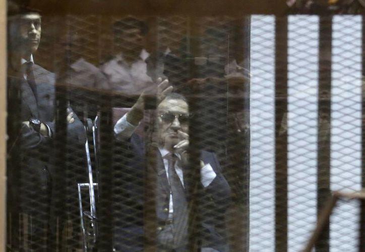 Hosni Mubarak, sentado, saluda a sus seguidores mientras asiste con sus dos hijos al veredicto en el caso de corrupción. (Agencias)