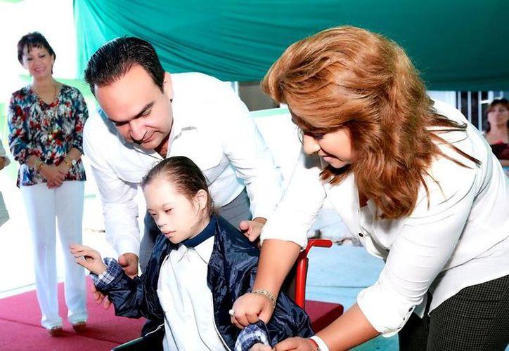 Los niños recibieron una chamarra para protegerse durante el invierno. En la foto la presidenta del DIF le coloca un abrigo a la niña  Idelmi Brito Canto, del sexto grado. (Milenio Novedades)
