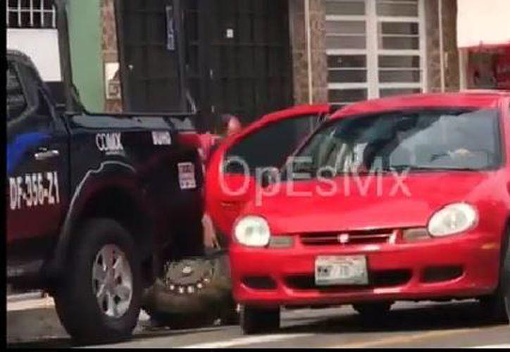 Tras robar la refacción, un sujeto se sube con todo y llanta a un auto y escapa. (Foto: Captura)