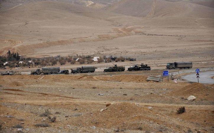 Esta foto, divulgada por la agencia noticiosa siria SANA, muestra a las fuerzas sirias durante un combate contra milicianos del grupo Estados Islámico en la ciudad de Palmira, cerca de Homs, en Siria. (SANA via AP)