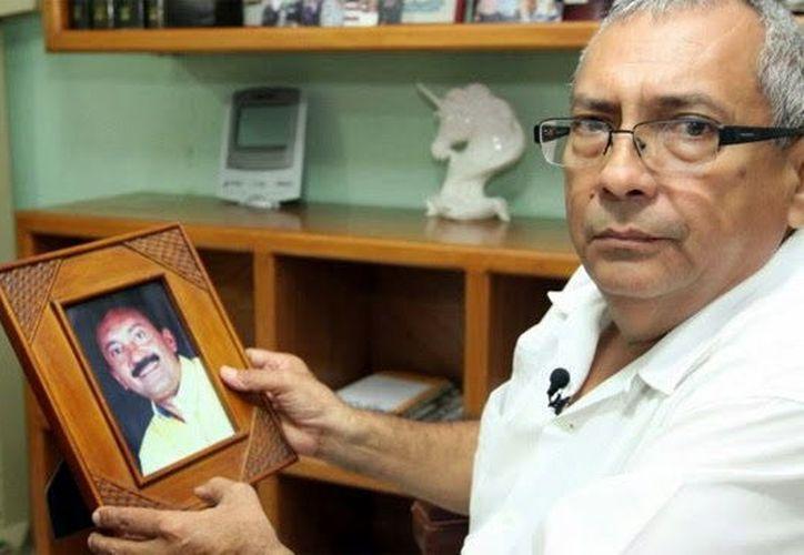 Alfonso Peniche Manzano con la foto de su hermano Delio. (Milenio Novedades)