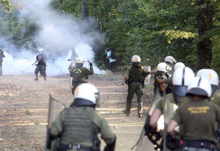 Policías antidisturbios y manifestantes se enfrentan en la localidad de Nees Skouries, al norte de Grecia. Los manifestantes protestan contra la apertura de una mina de oro en la zona. (EFE/Archivo)