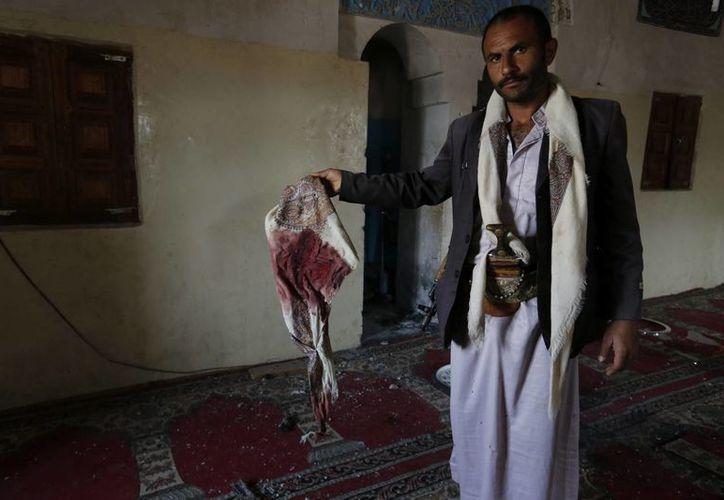 Un yemení muestra una tela cubierta de sangre mientras inspecciona la mezquita objeto de un ataque en el distrito de Bani Bahlol, al sur de Saná, Yemen. (EFE)