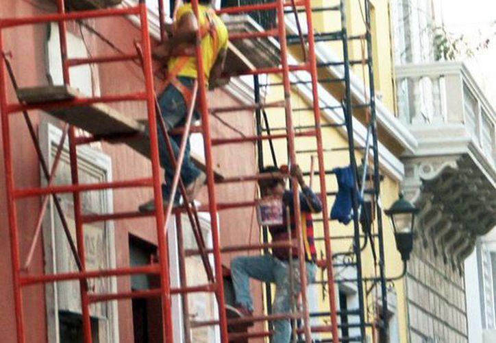 El pintor se cayó al romperse el andamio donde se encontraba. Imagen de contexto de un par de obreros que realizan los trabajos de remodelación, en el Centro histórico de Mérida.