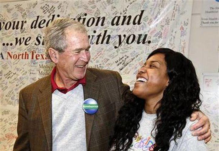 """El expresidente George W. Bush abraza a la enfermera que sobrevivió al ébola, Amber Vinson, en el Hospital Presbiteriano de Salud de Texas, en Dallas. Bush dijo en el libro de su autoría """"41: A Portrait of my Father"""", que su padre, George H. W. Bush consideró seriamente no buscar la reelección en 1992. (Agencias)"""