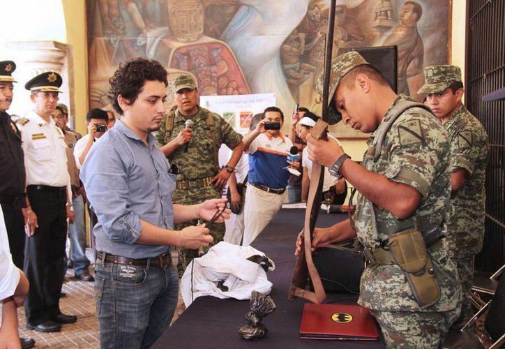 Un ciudadano canjea un arma en los bajos del Palacio Municipal, como parte de la campaña que realizaron el Ayuntamiento de Mérida y el Ejército. (SIPSE)
