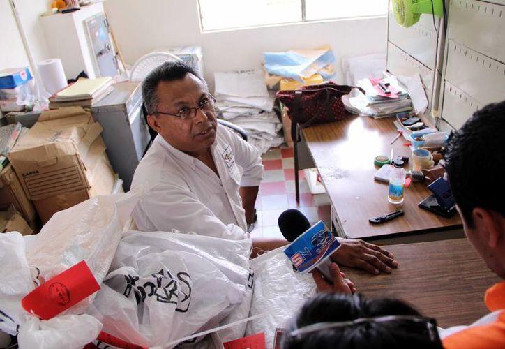 En la imagen José Menéndez, encargado de la oficina de Sepomex en Kanasín, en la cual se pueden observar miles de paquetes por entregar. (José Acosta/SIPSE)
