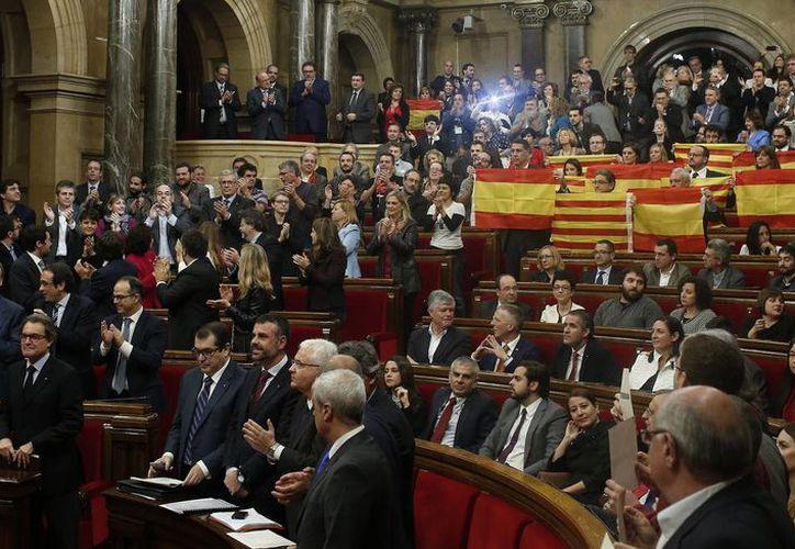 Legisladores del gobernante Partido Popular muestran banderas de España y Esteladas, el nombre por el que se conoce a la bandera independentista catalana, en el Parlamento catalán en Barcelona. (Agencias)