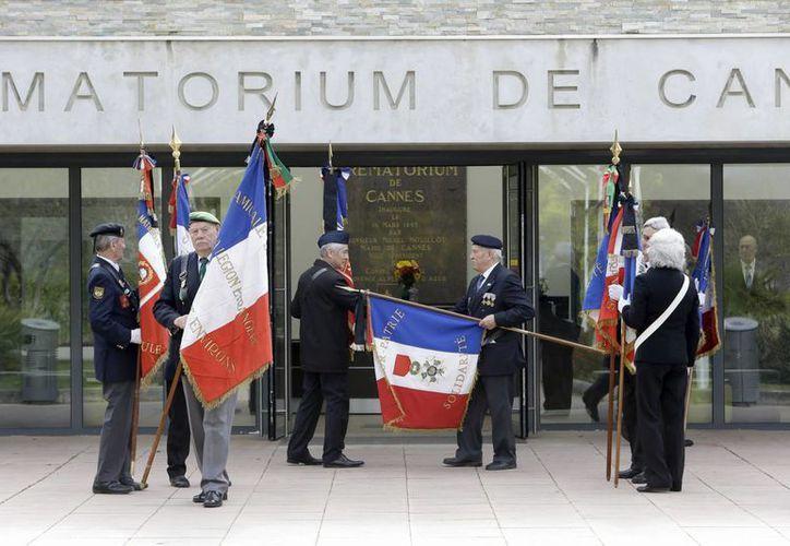 Veteranos de guerra exhiben las banderas francesas fuera del crematorio de Cannes, durante una ceremonia fúnebre para el coronel Gael Taburet, al sur de Francia. El fallecido fue el último piloto viviente de la escuadra. (AP Photo / Claude Paris)